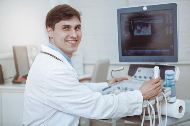 Gelukkige knappe mannelijke arts die aan de camera glimlachen, die aan de machine van de echoscopie bij zijn kliniek werken