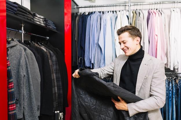Gelukkige knappe mens die jasje in de klerenwinkel bekijkt