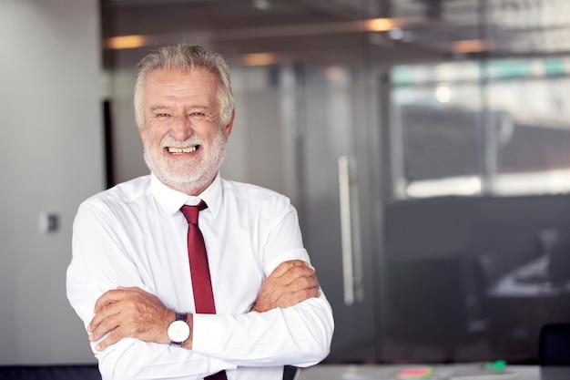 Gelukkige knappe oude zakenman die en zich in bureau bevindt glimlacht