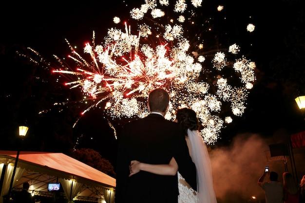 Gelukkige knuffelbruid en bruidegom kijken naar mooie kleurrijke vuurwerk nachtelijke hemel