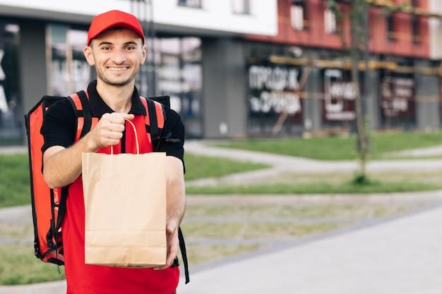 Gelukkige koerier is trots op zijn werk dat glimlachend op straat staat thuisbezorgd buitenportret