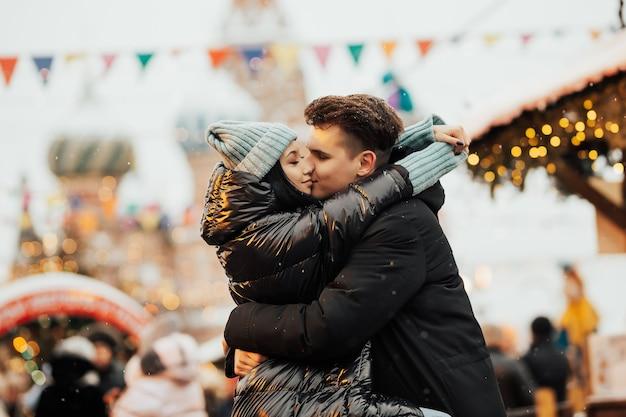 Gelukkige koppels op het stadsplein ingericht voor een kerstmarkt knuffelen en kussen