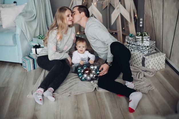 Gelukkige kussende ouders en baby onder kerstcadeaus
