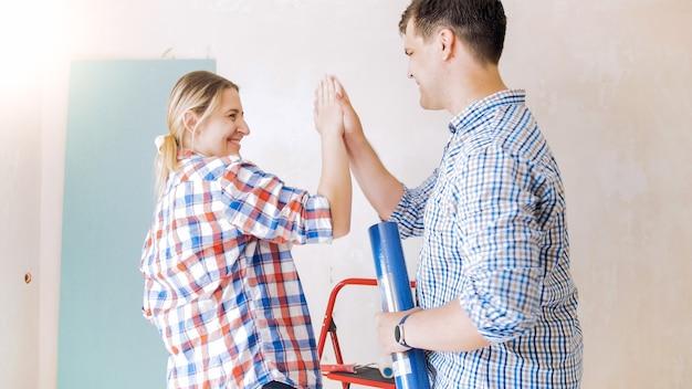 Gelukkige lachende familie die vijf aan elkaar geeft terwijl ze thuis renovatie doen.