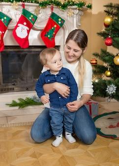 Gelukkige lachende moeder die haar zoontje knuffelt bij de kerstboom