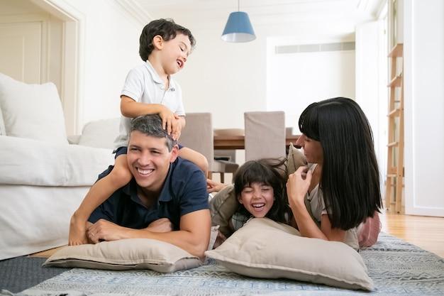 Gelukkige lachende ouders en twee kleine kinderen genieten van leuke tijd thuis
