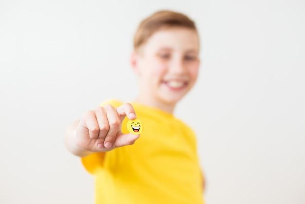 Gelukkige lachende tienerjongen met een gele glimlach in zijn hand.