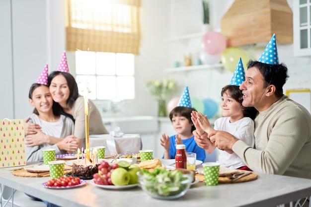 Gelukkige latijns-amerikaanse familie met kinderen die verrast zijn over vuurwerksterretje op een taart terwijl ze thuis samen verjaardag vieren. ouderschap, vieringsconcept