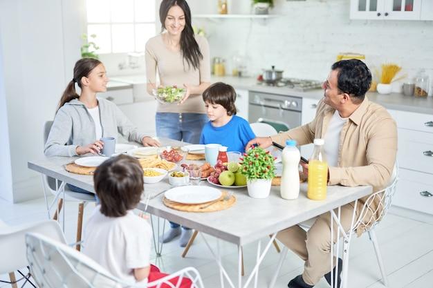 Gelukkige latijnse familie die thuis samen dineert. vrolijke vrouw die lacht terwijl ze salade serveert voor haar man en kinderen, staande in de keuken. selectieve focus