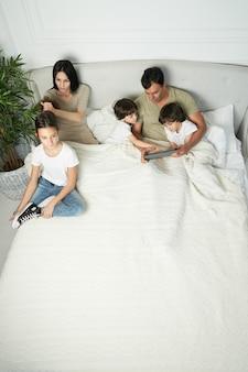 Gelukkige latijnse familie met schattige kleine kinderen begint de ochtend samen. liefdevolle ouders die tijd doorbrengen, met hun kinderen spelen, in bed blijven. ouderschap, technologieconcept