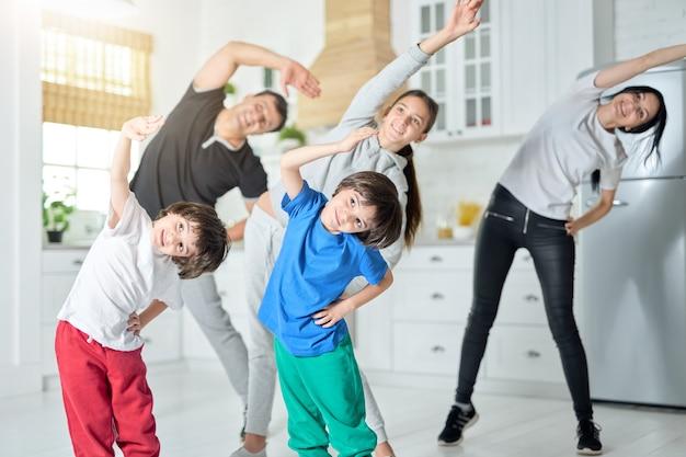 Gelukkige latijnse familie oefenen, ochtendtraining samen thuis. familie, sportconcept. selectieve focus op tweelingen