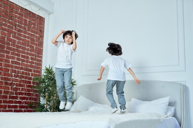 Gelukkige latijnse jongens, kleine broers die samen plezier hebben, thuis op het bed springen. kinderen, geluk, familieconcept