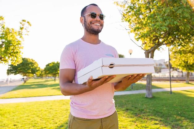 Gelukkige latijnse mannelijke koeriers dragende pizza in park