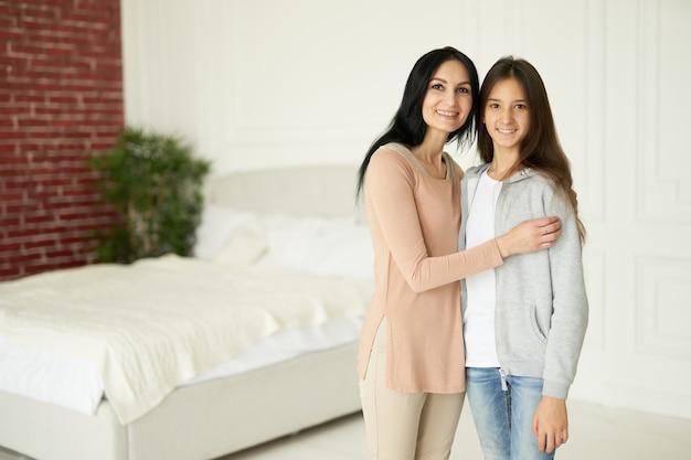 Gelukkige latijnse moeder en dochter glimlachen naar de camera, kijken aanhankelijk terwijl ze samen binnenshuis poseren. familie, kinderen concept