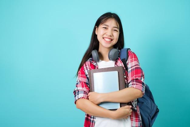 Gelukkige leerling. vrolijk aziatisch meisje glimlachend naar de camera staande met rugzak in studio op blauwe achtergrond. terug naar schoolconcept.
