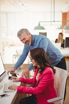 Gelukkige leidinggevenden die met elkaar in wisselwerking staan terwijl ze aan het bureau werken