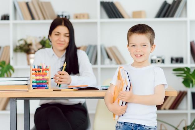 Gelukkige leraar die glimlachend meisje privélessen geeft na school