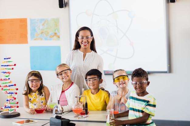 Gelukkige leraar en leerlingen die voor de camera stellen