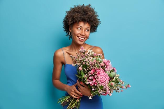 Gelukkige leraar poseert met een groot mooi boeket bloemen ontvangen van leerlingen, kijkt met plezier opzij, is dol op fris, aangenaam aroma, geniet van favoriete geur, draagt blauwe jurk, staat binnen.