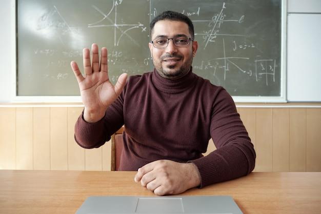 Gelukkige leraar van gemengd ras begroet online studenten per werkplek