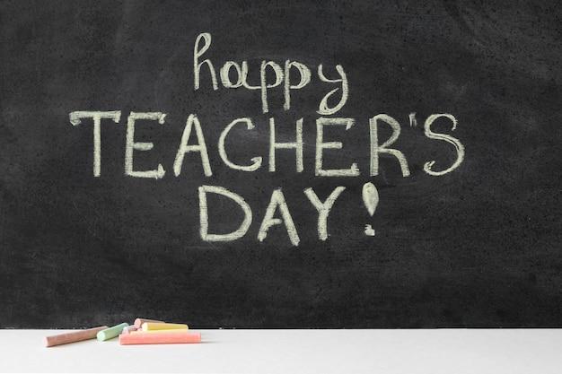Gelukkige lerarendag die met krijt op bord wordt geschreven