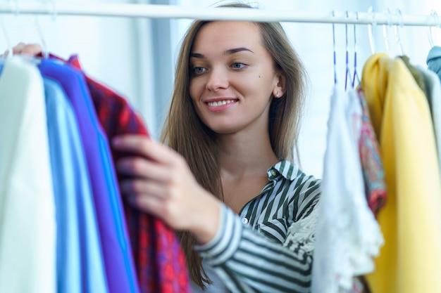 Gelukkige leuke donkerbruine vrouw die zich dichtbij garderoberek vol modieuze trendy kleren op hangers en huisspullen bevinden die en uitrusting voor speciale gelegenheid kiezen zoeken.