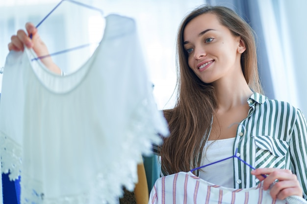 Gelukkige leuke jonge donkerbruine vrouw die zich dichtbij het rek van de garderobekast vol modieuze trendy kleren op hangers bij toonzaal bevinden en uitrusting kiezen