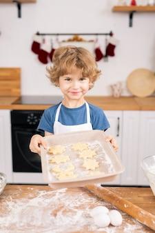 Gelukkige leuke jongen die dienblad met rauwe zelfgemaakte koekjes houdt terwijl hij aan de keukentafel staat