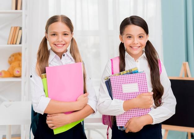 Gelukkige leuke schoolmeisjes die met voorbeeldenboeken glimlachen