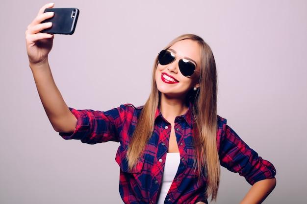 Gelukkige leuke vrouw die selfie maakt die over grijze muur wordt geïsoleerd.