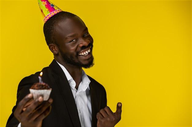 Gelukkige leuke zwarte die bij camera glimlacht en een verjaardagscake houdt
