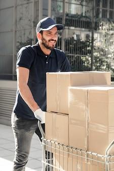 Gelukkige leveringsmens die met kartondozen op stoep lopen