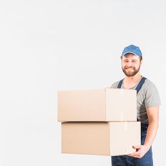 Gelukkige leveringsmens die zich met grote dozen bevinden