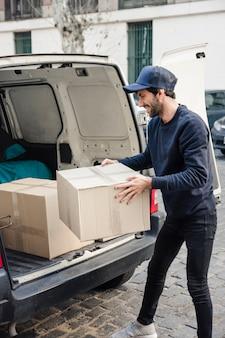 Gelukkige leveringsmens dragende kartondoos dichtbij voertuig