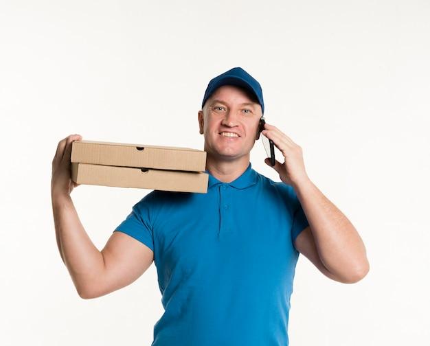 Gelukkige leveringsmens dragende pizzadozen en het houden van telefoon