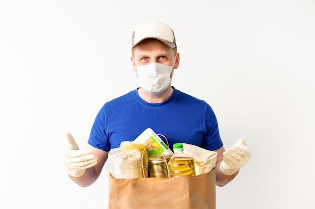 Gelukkige leveringsmens in de blauwe zak van de de handgreep van de glb lege t-shirt eenvormige handschoen op geïsoleerd. service quarantaine pandemisch coronavirus virus 2019-ncov. donatie eten