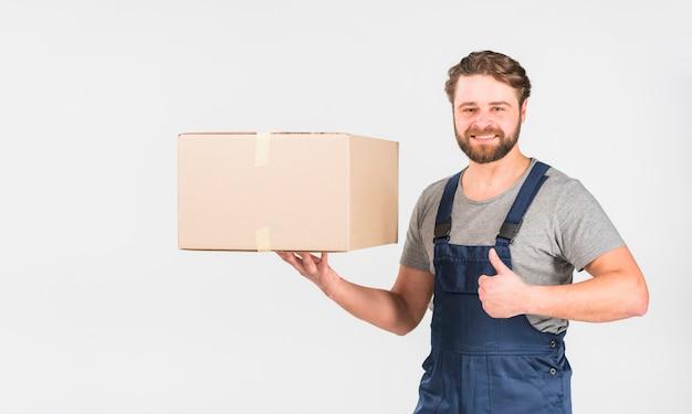 Gelukkige leveringsmens met doos die duim toont