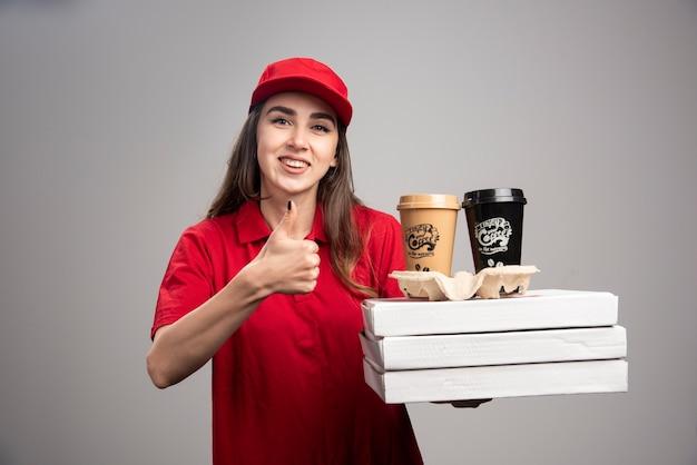 Gelukkige leveringsvrouw die duimen met pizza en koffiekopjes op grijze muur maken.