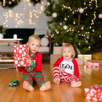 Gelukkige lieve kinderen in pyjama's spelen met kerstcadeautjes
