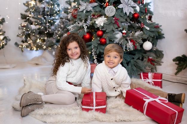 Gelukkige lieve kinderen met geschenkdozen in hun handen in de buurt van de kerstboom en licht