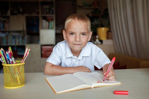 Gelukkige linkshandige jongen die in het papieren boek schrijft met zijn linkerhand internationale linkshandige dag