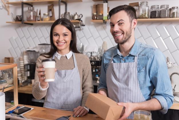 Gelukkige maaltijd. aangenaam jong stel met doos en kopje koffie en glimlachend terwijl ze achter de bar staan.