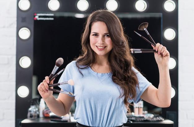 Gelukkige make-upkunstenaar met borstels