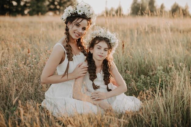 Gelukkige mamma en dochter die en op het gras op het gebied in de zomer glimlachen koesteren