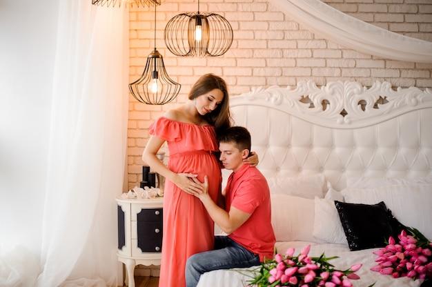 Gelukkige man die aan de buik van zijn mooie zwangere vrouw luistert