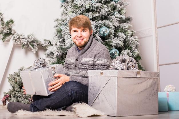 Gelukkige man die een cadeau thuis in de buurt van de kerstboom opent.