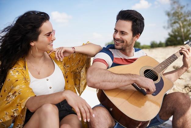 Gelukkige man die gitaar speelt voor mooie vrouw