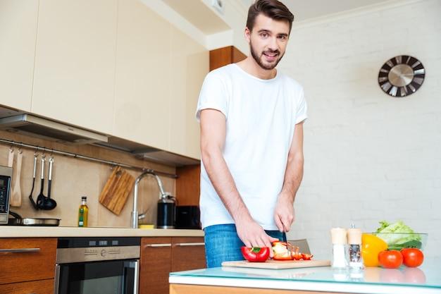 Gelukkige man die groenten snijdt in de keuken