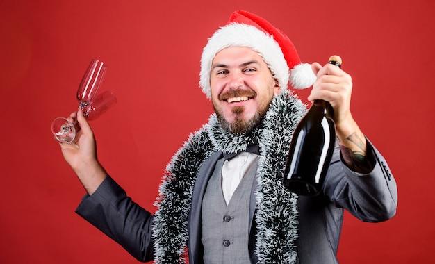 Gelukkige man die kerstmis viert. zakelijk nieuwjaarsfeest. zakenman in kerstmuts met klatergoud. kersttijd voor de lol. man pak champagne drinken uit glazen. proost. kerstvakantie.