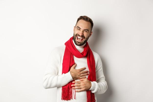 Gelukkige man die lacht en de buik aanraakt, grinnikt van grappige grap, staande in de wintertrui en rode sjaal, witte achtergrond.